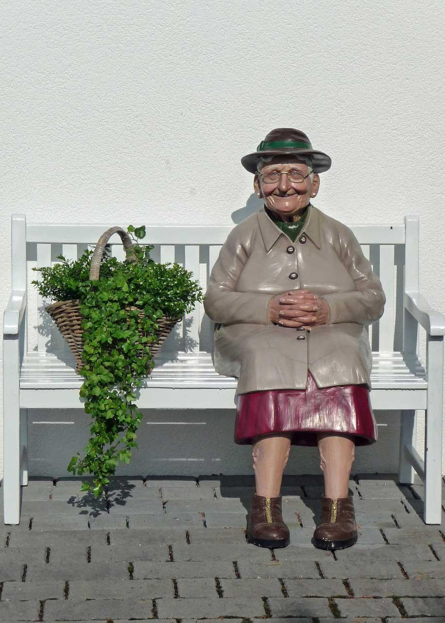 Figura starice na klupi i korpa sa cvecem